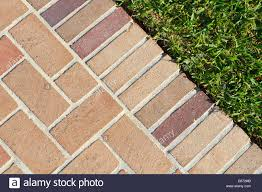 Brick Pavers Pictures by At The Edge Of A Nice Clean Brick Pavers Walkway And Lush Green