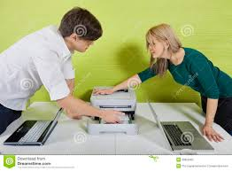 Laptops Desk by Side View Of Young Businesspeople Setting Up Printer With Laptops