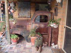 planted cars whiskey barrels and garden