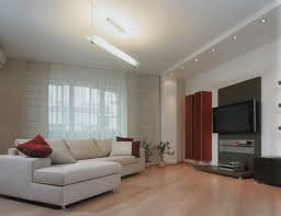 white fabric sofa on brown wooden laminate floor connected by lcd