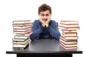 Picture Of Student Sitting At Desk Studio Shot Of Angry Stressed Student Sitting At His Desk With