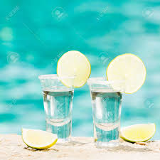 margarita on the beach two tequila shots with sliced lime on the beach transparent