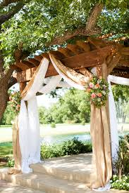 wedding arches decorated with burlap burlap draping with country pink and green flowers a wooden