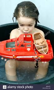 child children kid boy kids playing with a red toy boat in a tub