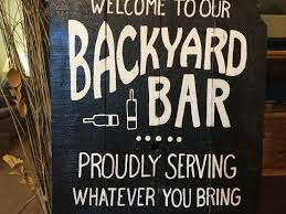 welcome to our backyard bar sign proudly serving whatever you