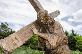 a detailed size statue of jesus carrying the cross in the