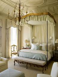 french style bedroom with wrought iron chandelier and canopy bed