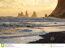 sunset with golden sky behind the reynisdrangar rocks vik black