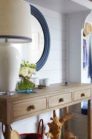 239 best coastal homes interiors images on pinterest coastal beach bungalow foyer features a round blue rope mirror lining a shiplap wall lined with a wood 3 drawer console table adorned with knotted rope knobs and
