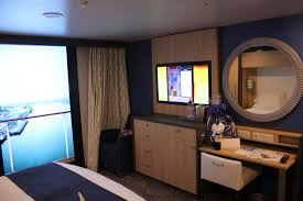 photo tour of category l large interior stateroom with virtual screen television across from the bed as well as a dresser below the television that has drawers for clothing and is also home to your mini fridge
