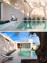 a small pool is positioned between a house and studio space with