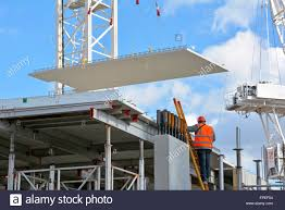 construction site worker on ladder as crane positions large