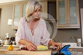 femmes plus cuisine une femme plus âgée dans la cuisine recherchant la recette sur le