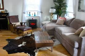 interior faux leopard skin rug with black leather sofa on wooden