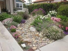 small front yard with ornamental plants river rocks modern garden