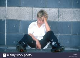 8 year boy looking depressed sad uk stock photo