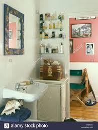 Glass Shelving Bathroom by Perfume Bottles On Glass Shelves Beside Open Door In Small White