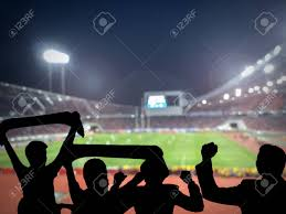 how tall are football stadium lights silhouettes of football fans cheeringagainst large football stadium