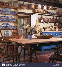 copper pans and blue white china on shelves in cottage dining room