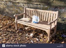 Wooden Park Bench Tesco Carrier Bag And Rubbish Left On Wooden Park Bench Stock