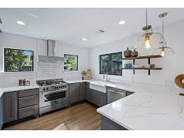 cote de texas i believe this is quartzite on the counters love the stove another industrial touch wood shelving instead of cabinets white subway tiles flanked by