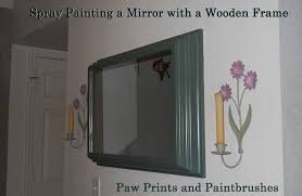 paw prints and paintbrushes spray painting a mirror with wooden frame