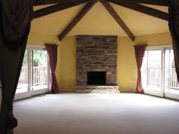 6 sided room with vaulted ceiling and beams