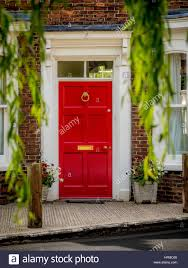 red front door on house seen through weeping willow branches in