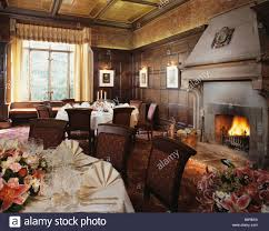 lighted fire in large fireplace in paneled country hotel dining