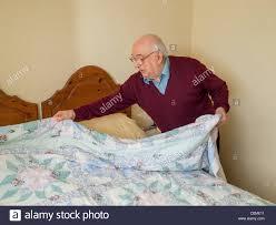 elderly man making his bed stock photo royalty free image