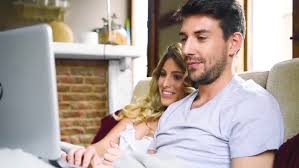 young couple in bed shopping online using digital tablet