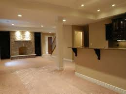 basement carpet flooring and fireplace with staircase railings