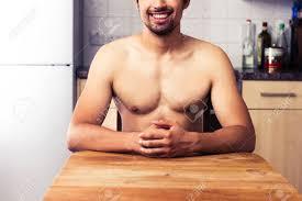 homme nu cuisine homme nu est assis à la table dans la cuisine les mains jointes