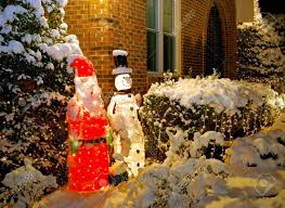 outdoor santa and snowman decorations covered in snow stock photo