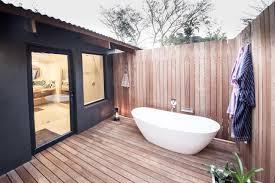 unique outdoor bathroom with wood pathway and sliding glass door