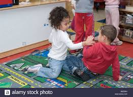 4 year and boy fighting a in school stock photo