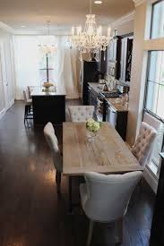 small narrow dining table under chandelier above wood floor around