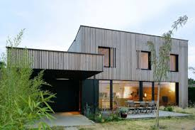garage modern square house with wood trim facade and black garage modern square house with wood trim facade and black garage door also wonderful wooden terrace with wooden seats and simply garden design