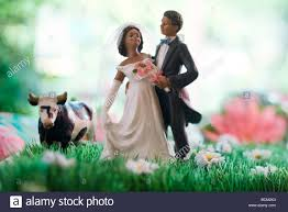 and groom figurines and groom figurines standing in field of flowers plastic