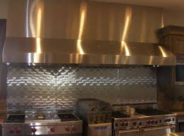 interesting stainless steel vent hood with tin backsplash and