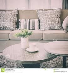sturdy brown tweed sofa with grey patterned pillows stock photo