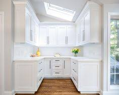 lovely kitchen with white shaker style cabinets close calm wall on
