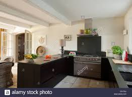 lacanche cooker and dark wood units in stone floored kitchen with