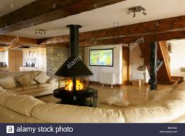 living room with large cream sofa and central circular lit fire