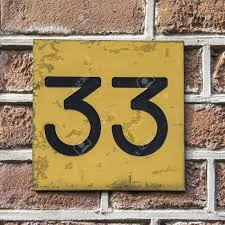 house number thirty three engraved in a gold colored plastic
