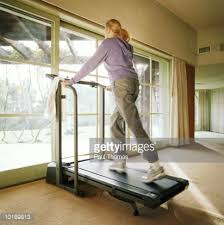 treadmill in living room woman exercising on treadmill in living room rear view stock photo