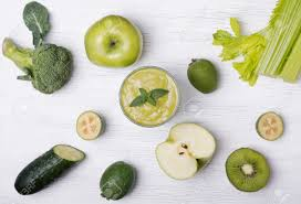 cutted and whole green colored fruits and vegetables on the white