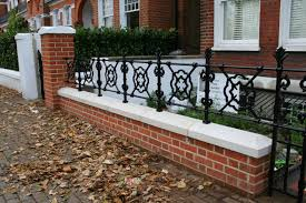 stylish red brick wall and black railings in london front garden