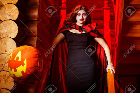 halloween background long vampire woman in cloak is standing indoors at stairs with red