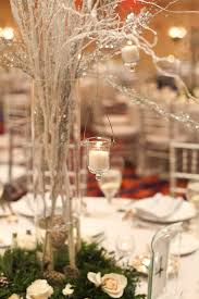 tall centerpieces wth silver branches hanging votives sitting in